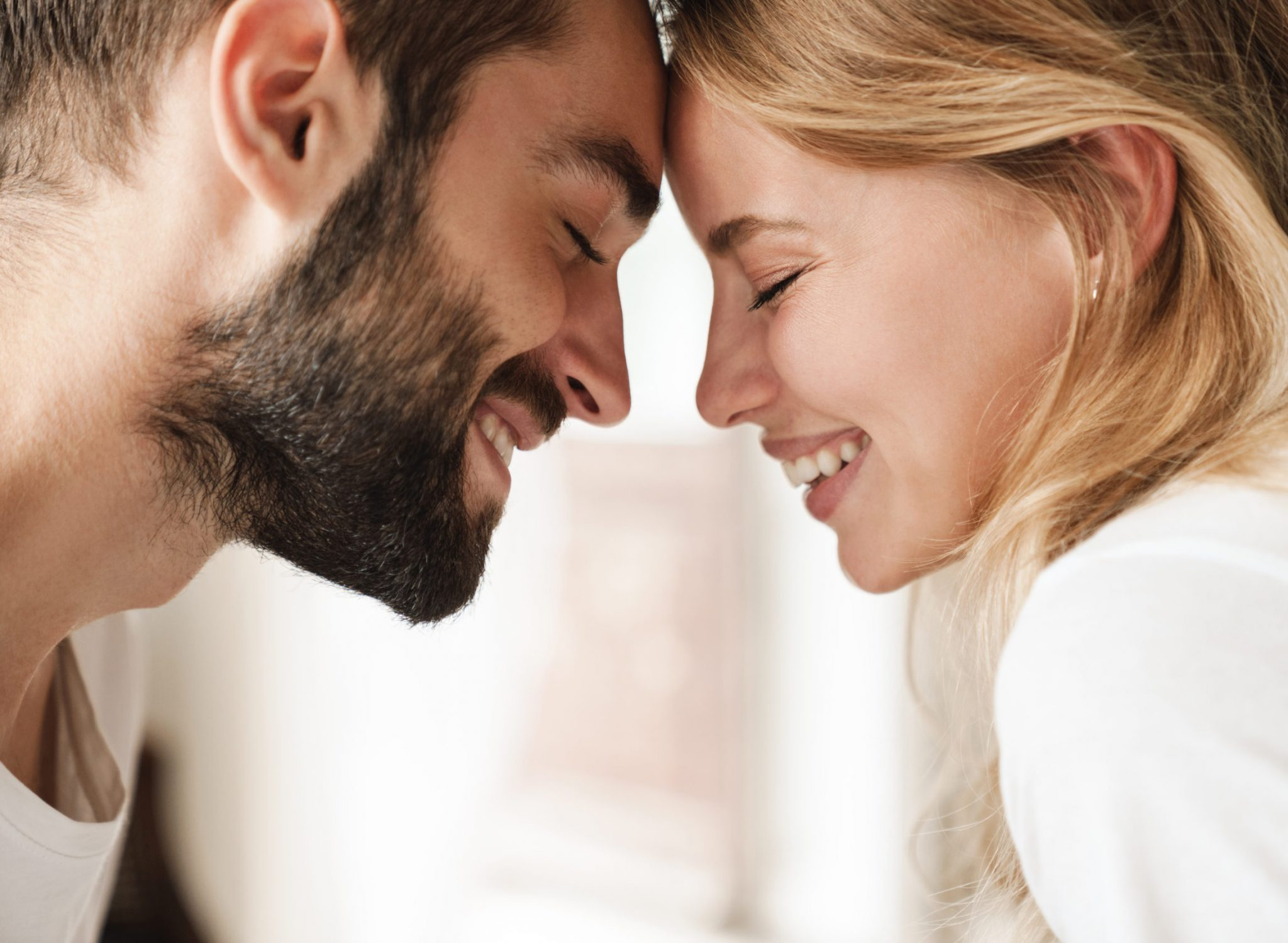 Close up of a beautiful happy young couple relaxing at home, embracing